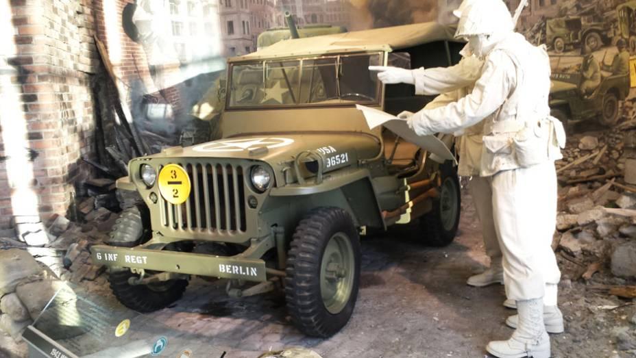 O lendário Jeep Willys aparece em trajes de guerra no meio de um ambiente que reproduz ruínas de uma construção