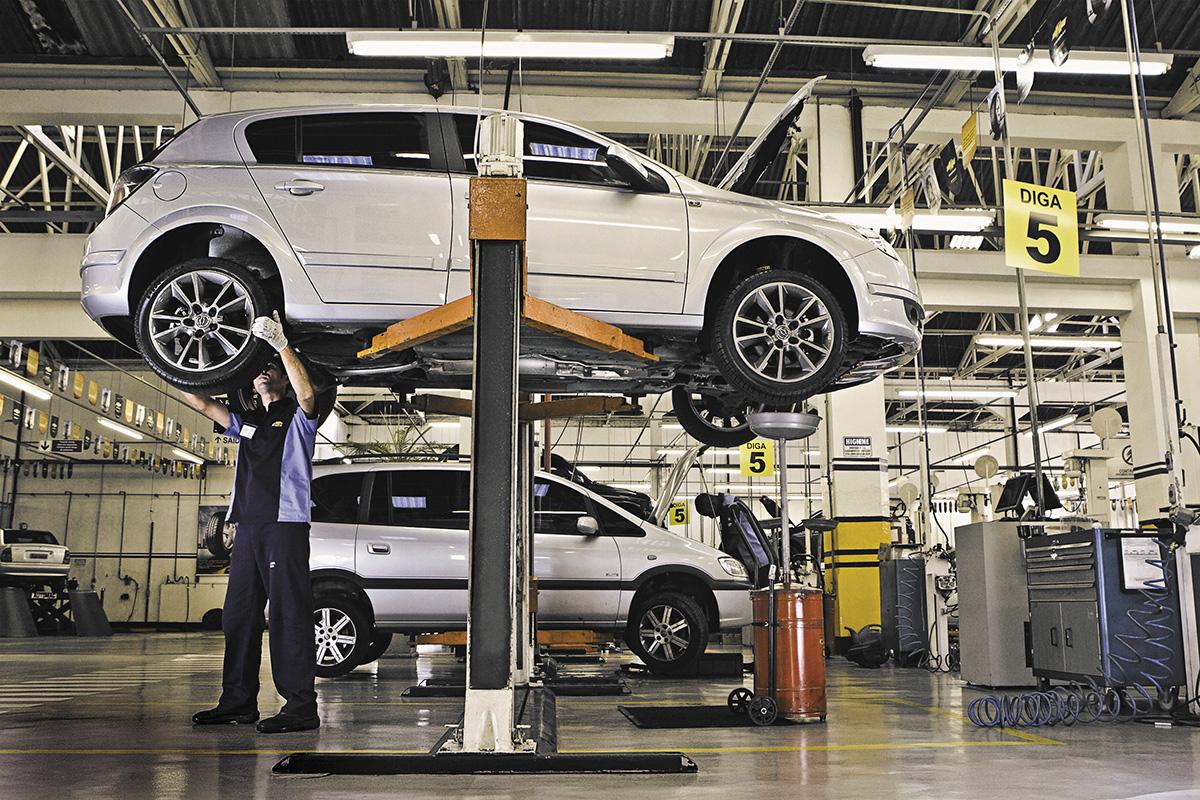 Mecânico faz manutenção no freio em oficina de serviço expresso da Chevrolet
