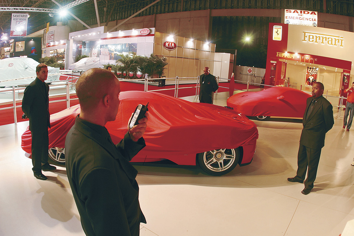 Seguranças vigiando as Ferrari Enzo no estande da marca, antes da abertura do Sa