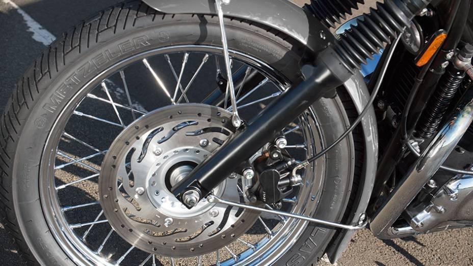 """Bons pneus, um disco frontal e rodas raiadas na versão T100   <a href=""""http://quatrorodas.abril.com.br/moto/testes/triumph-bonneville-t100-741213.shtml"""" rel=""""migration"""">Leia mais</a>"""