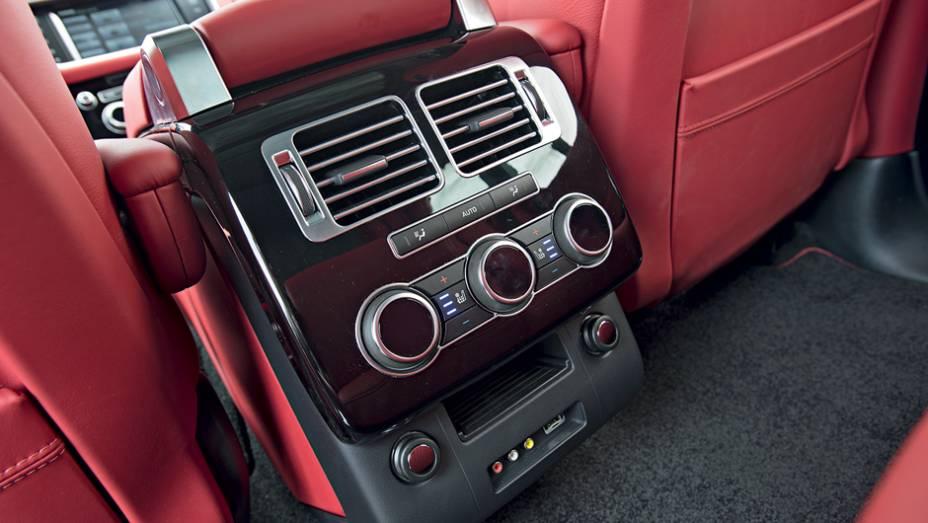 """Atrás, um console abriga controles de ventilação e entrada auxiliar   <a href=""""http://quatrorodas.abril.com.br/carros/testes/land-rover-range-rover-vogue-738240.shtml"""" rel=""""migration"""">Leia mais</a>"""