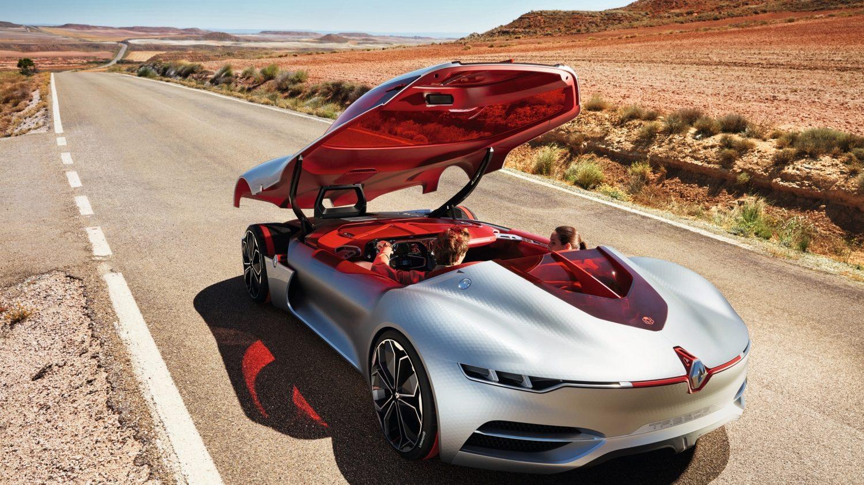 Renault Trezor, um carro-conceito elétrico, prateado. Ele não tem portas, uma tampa inteiriça cobre a cabine e integra o capô, vidros e teto. Pneu com faixa vermelha aparece com essa tampa aberta