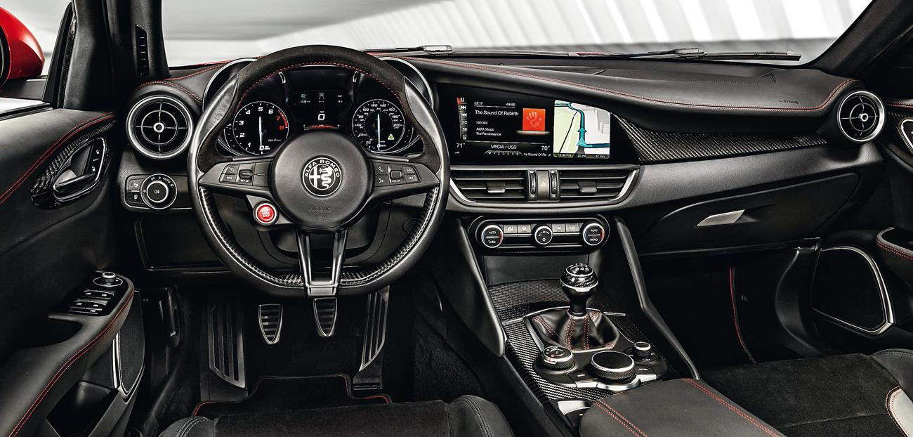 No painel, os comandos estão voltados para o motorista. O botão (vermelho) de partida fica no centro do volante