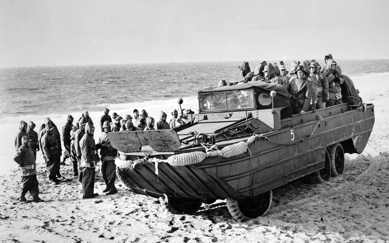 Um veículo anfíbio DUKW carregado com tropas desembarca no litoral francês