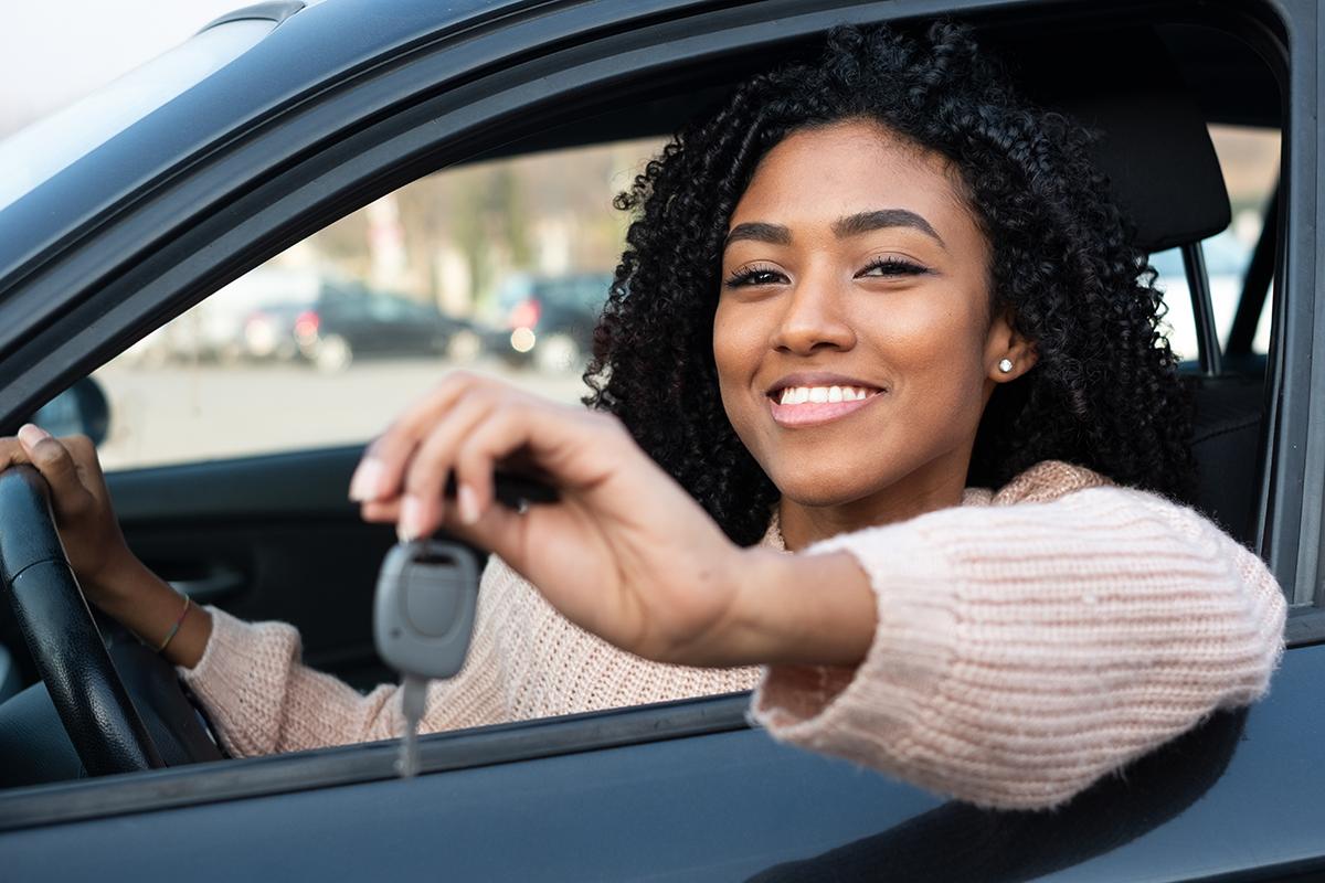Mulher Preta Sorrindo Segurando chave de carro dentro do veículo. Karvi, plataforma online para vendas de carro.
