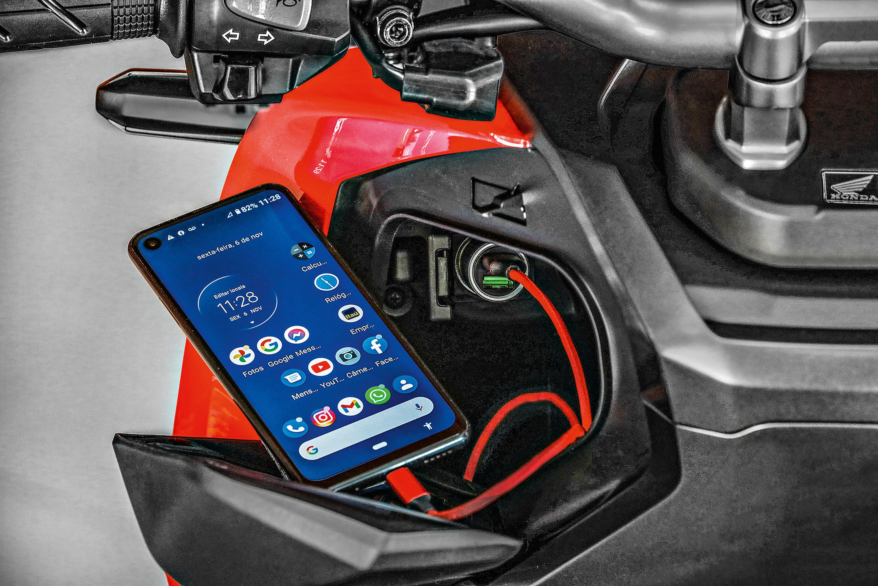 Celular sendo carregado no painel da Honda ADV