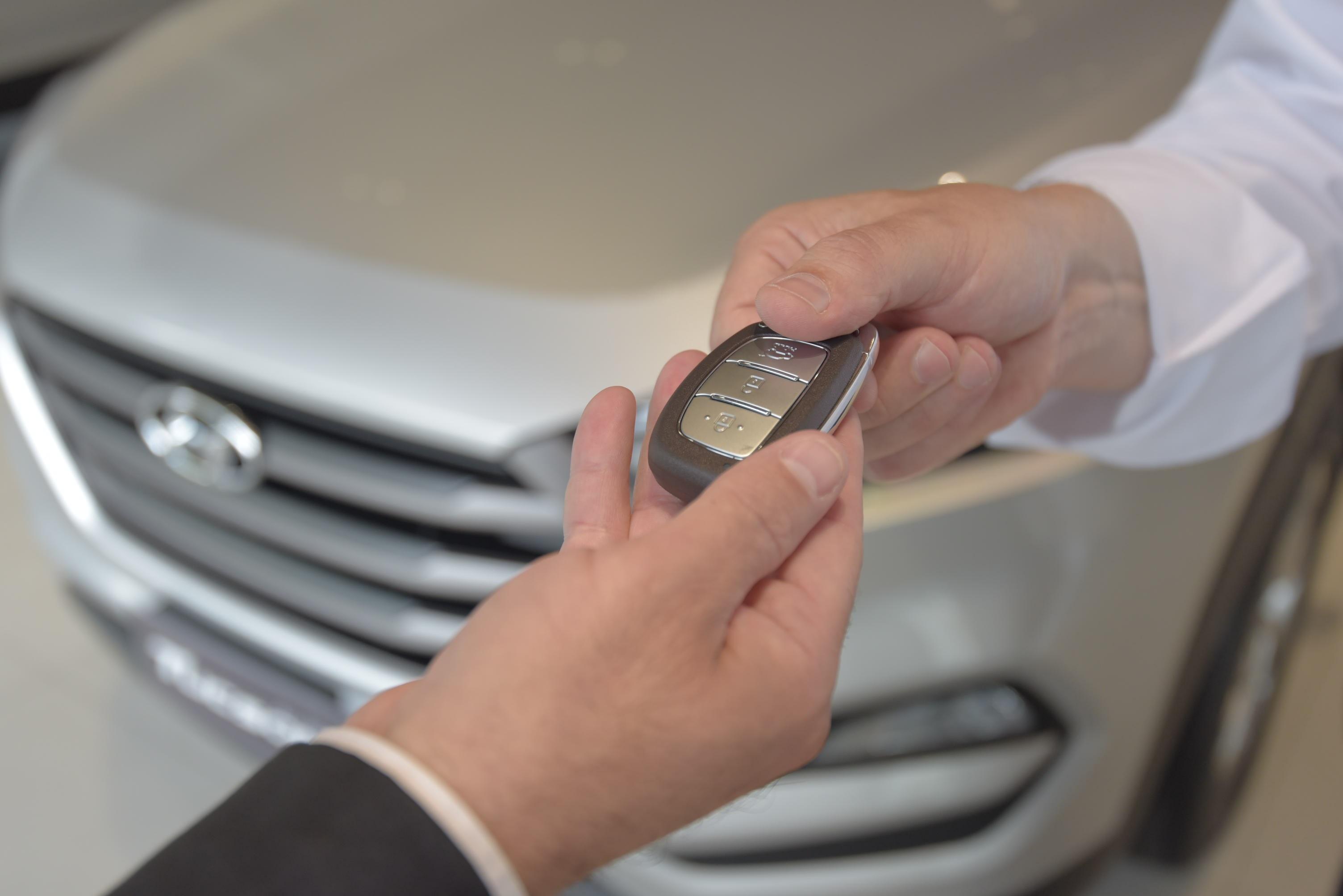 Vendedor entrega chave do carro para cliente
