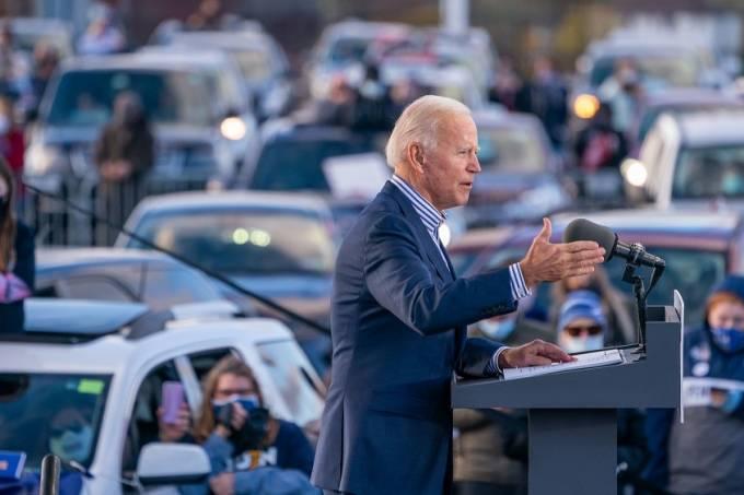 Joe Biden com carros ao fundo 2020