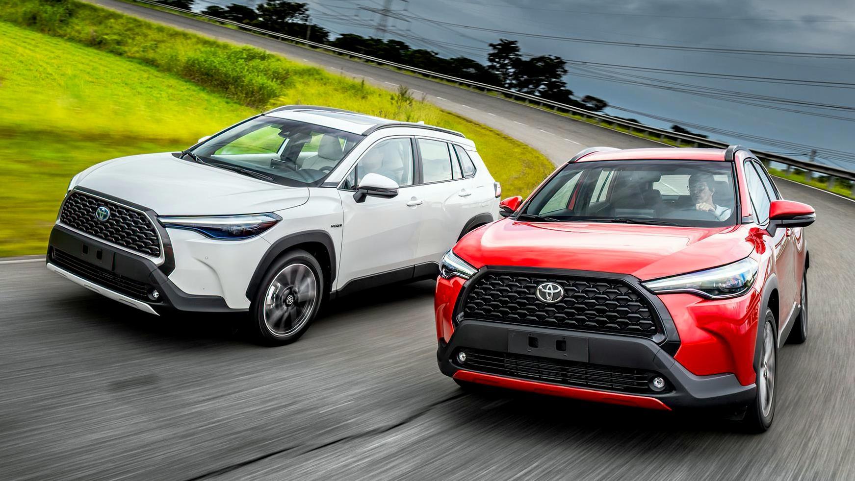 Dois Toyota Corolla Cross 2.0 XRE, um branco e outro vermelho, vistos de 3/4 de frente
