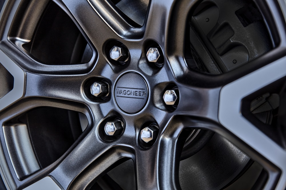 All-new 2022 Wagoneer standard 20-inch aluminum wheels featuring a multitude of finishes and textures. A three-dimensional wheel cap highlighting the Wagoneer logo is suspended in acrylic.