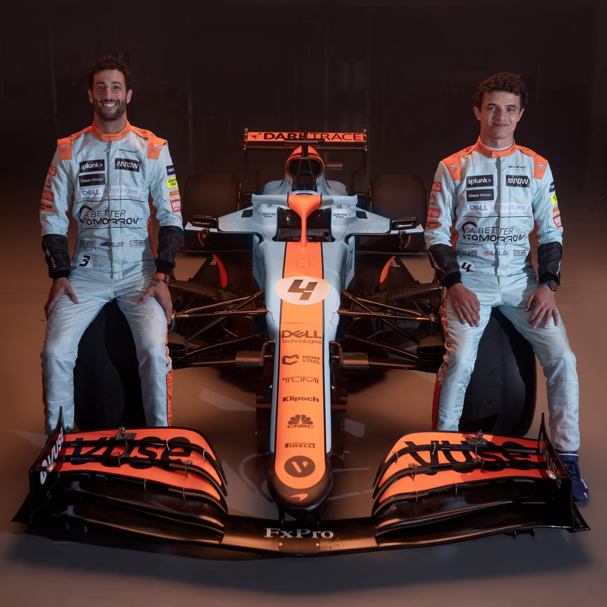 Daniel Ricciardo e Lando Norris sentados no carro de Fórmula 1 da McLaren visto de frente