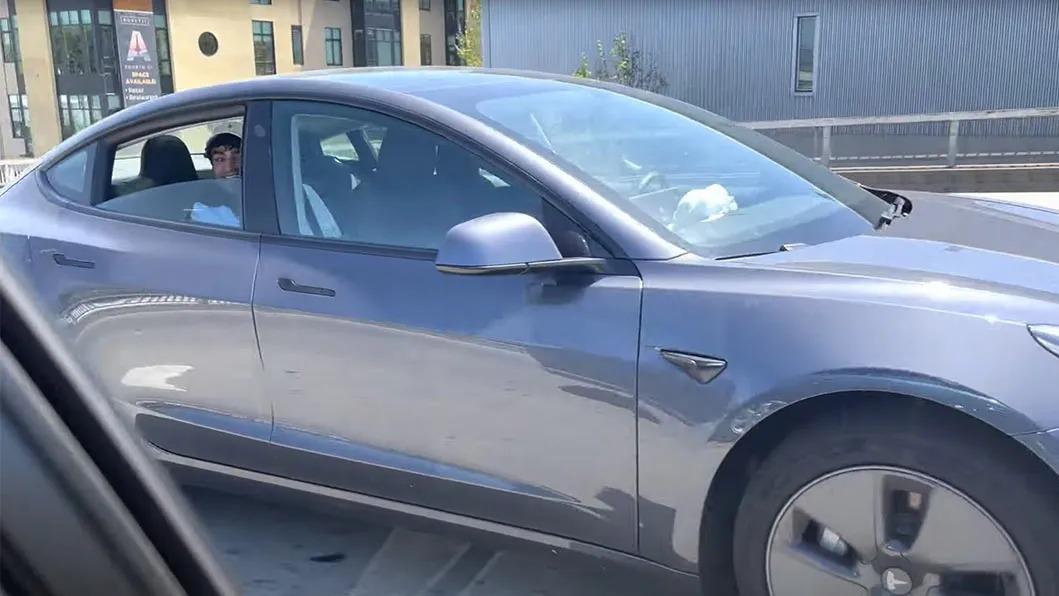 Tesla Model 3 cinza visto de lado com jovem no banco de trás