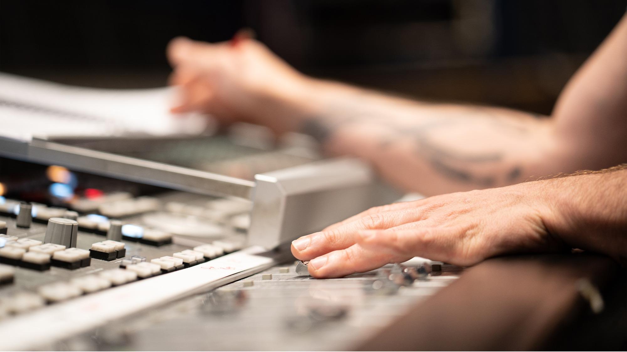 Mão em mesa de edição de som