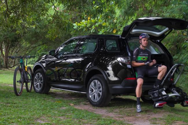 Henrique Avancini apoiado em um carro Land Rover
