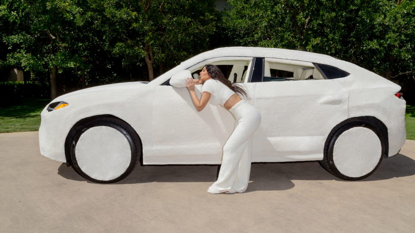 Lamborghini Urus coberto por tecido sintético branco visto de lado