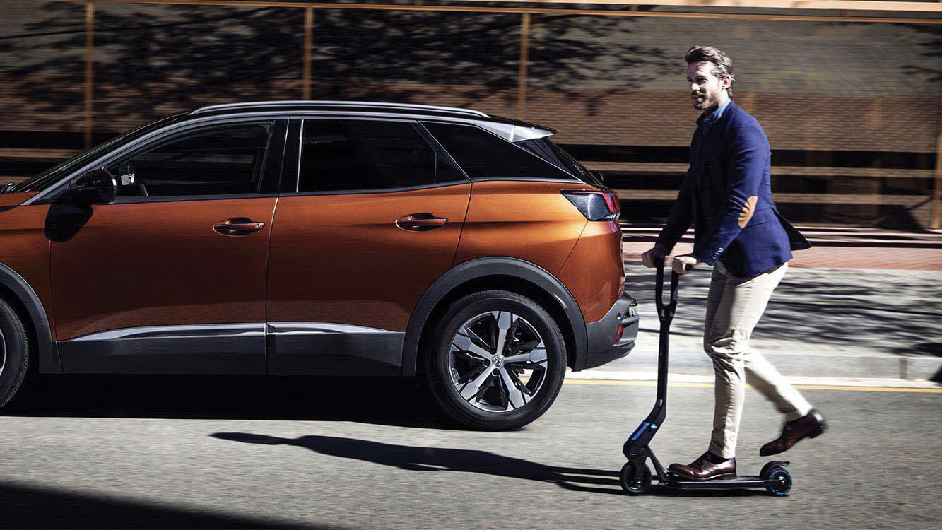 Patinete elétrico da Peugeot ao lado do modelo 3008 marrom