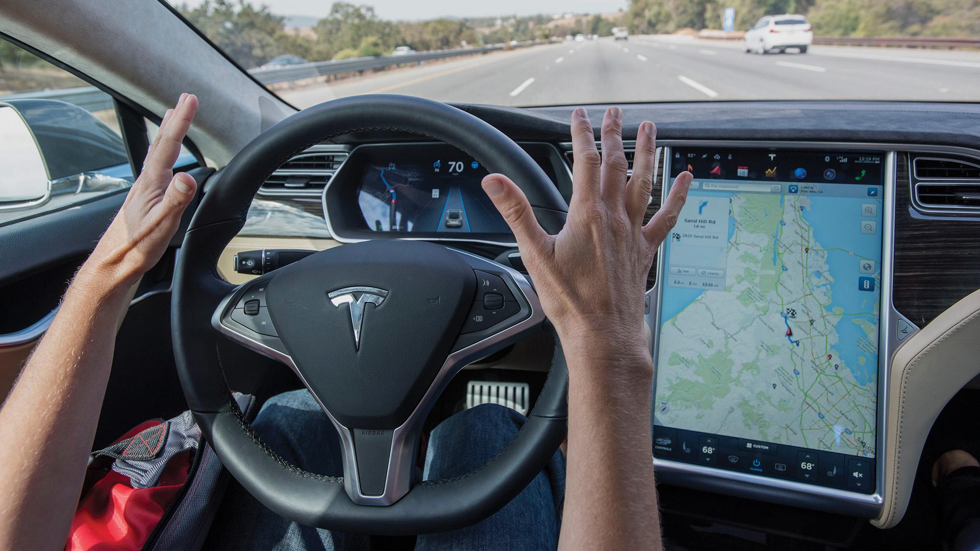 Motorista sem as mãos no volante fazendo demonstração do Autopilot