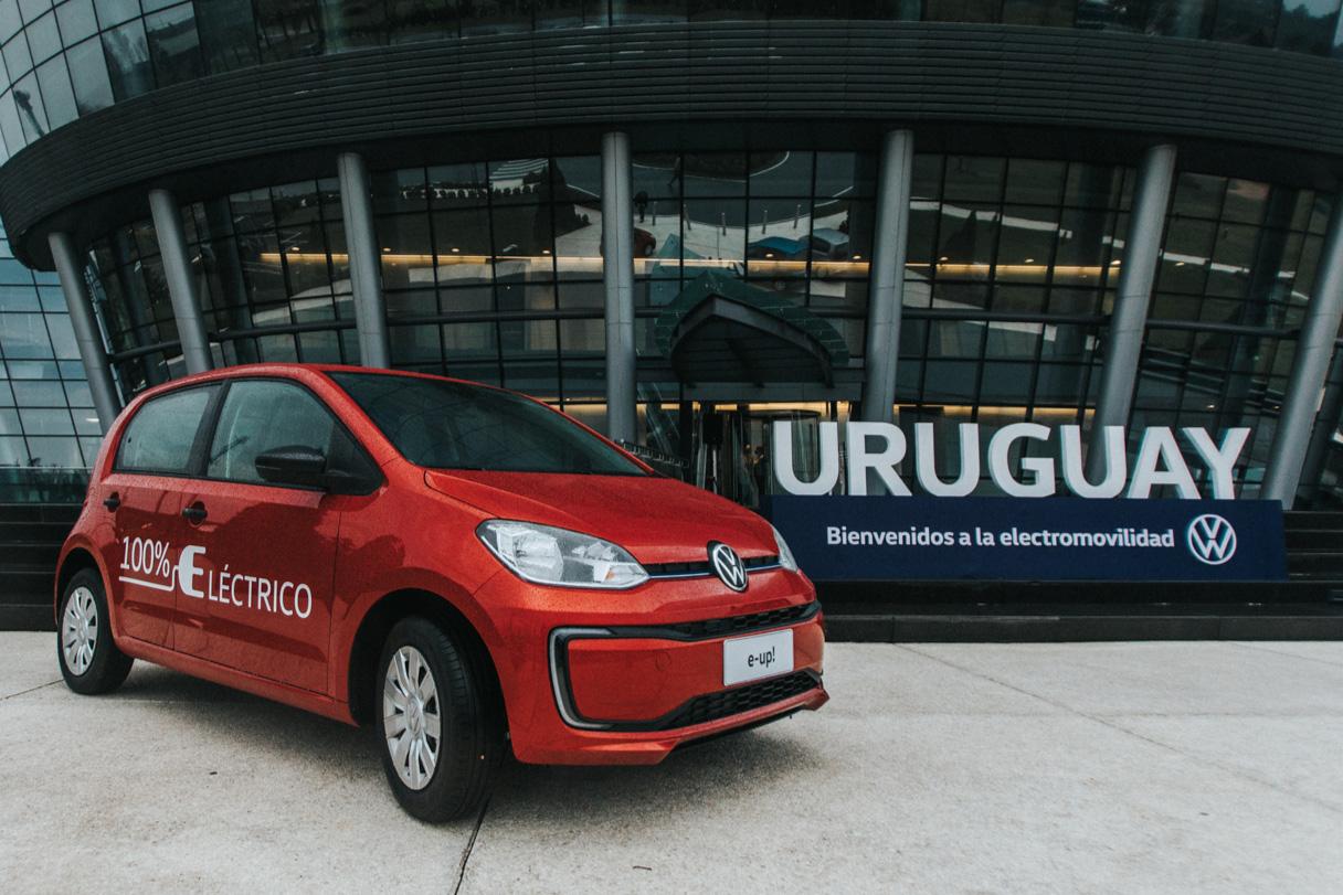 VW e-UP elétrico laranja com placa do Uruguai ao fundo