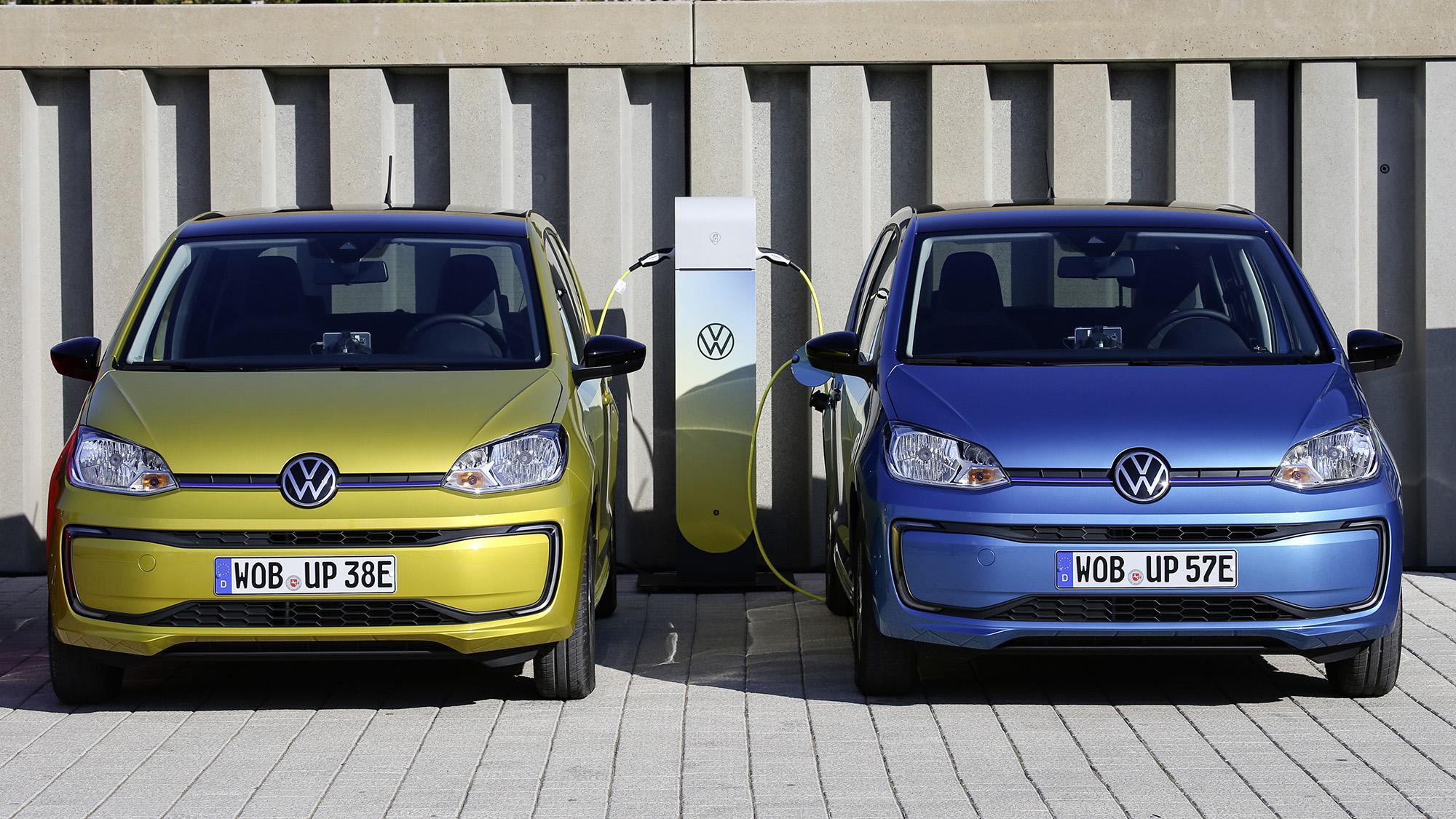 Dois VW e-Up!, um azul e outro amarelo carregando vistos de frente