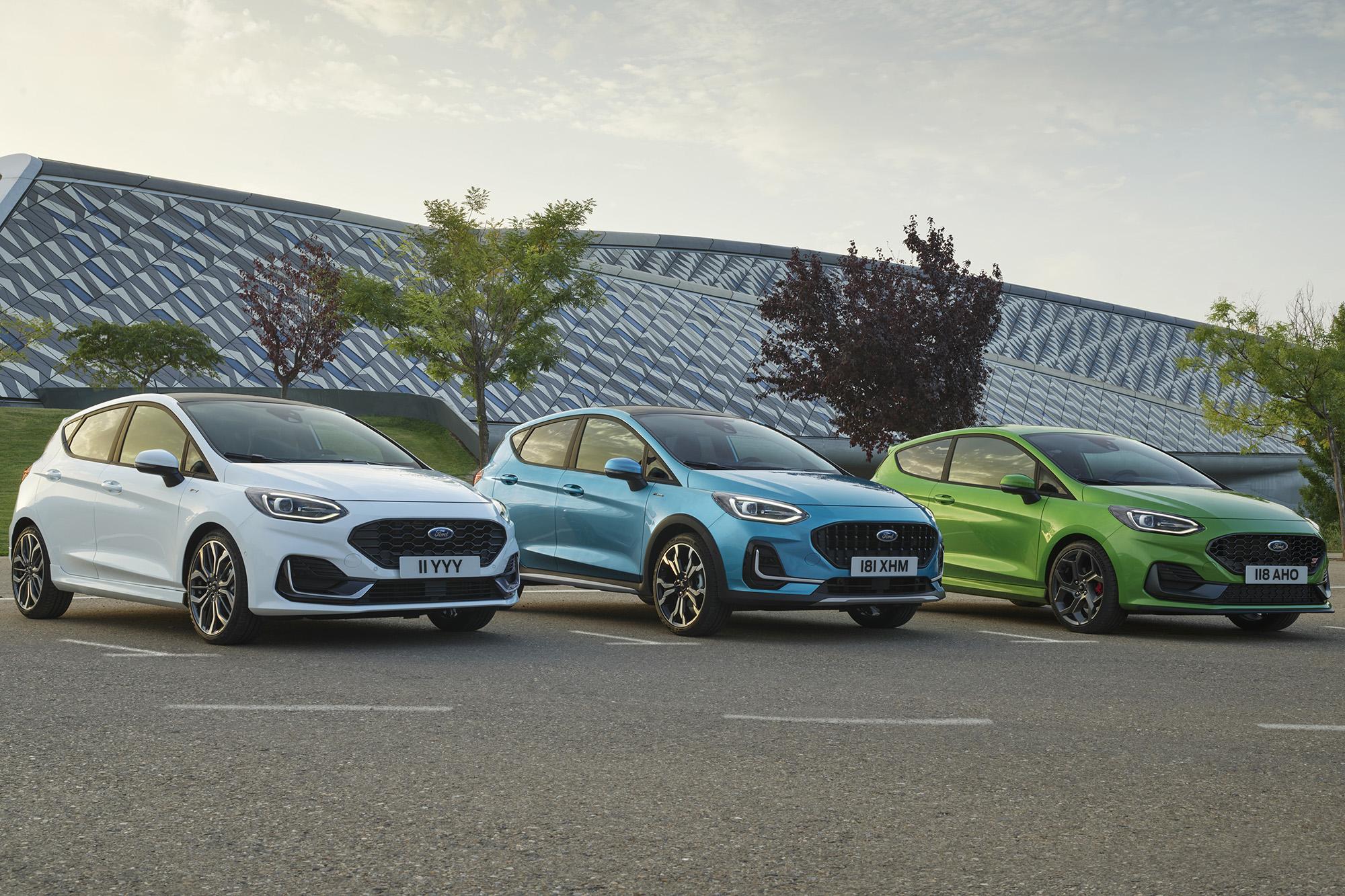 Três Ford Fiesta 2021 branco (esquerda), azul (meio) e verde (direita) vistos 3/4 de frente